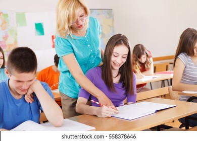 Teacher helping a cute girl with the schoolwork in the classroom. Young boy next to her is smiling
