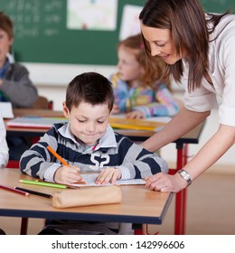 Teacher helping elementary student at the classroom