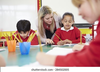 Teacher Helping Female Pupil With Writing Reading At Desk
