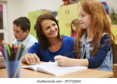 Teacher helping her cute pupil