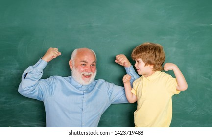 Teacher helping his teen pupil on education class. Concept of education and teaching. Portrait of confident old male teacher. Happy Pupil with over blackboard background