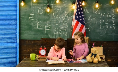 Teacher helping kids with computers in elementary school on the USA national flag background. Pupil is having one-on-one time with his instructor. Elegant man on the background with flag of the USA.