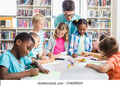 Teacher helping kids with their homework in library at school