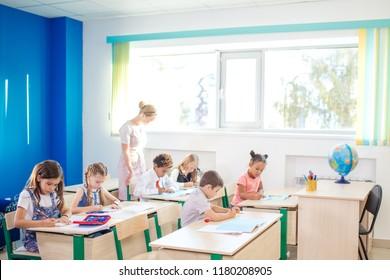 A teacher helping school childs in class or chek homework