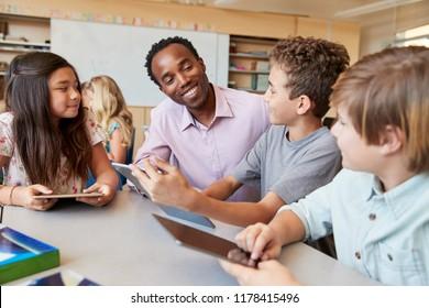 Teacher helping school kids using tablet computers in class