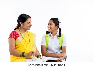 Teacher helping schoolgirl with book.