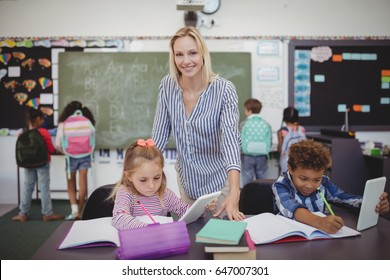 Teacher helping schoolkids with their homework in classroom at school