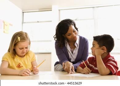 Lehrer hilft Schülern mit Schularbeit im Schulunterricht. Horizontal gerahmte Aufnahme.