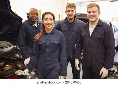 Teacher Helping Students Training To Be Car Mechanics