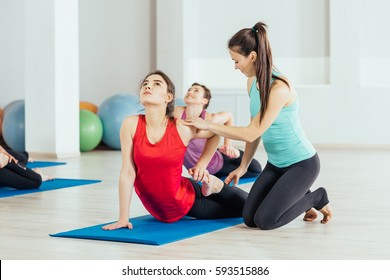 teacher helping with yoga pose indoors.fitness, sport, people and healthy lifestyle concept