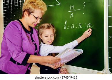 A teacher and her student during class at school. Education.