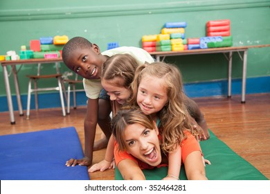 teacher with hers students playing on the floor