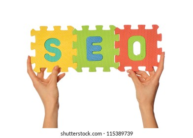 teacher holding in the hand the amusing colored puzzles with word SEO