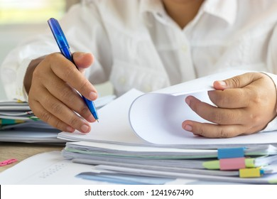 Teacher holding pen by hand for checking student homework assignments on desk in school office. Unfinished paperwork stacked in archive with color binder paper clips. Education and business concept.