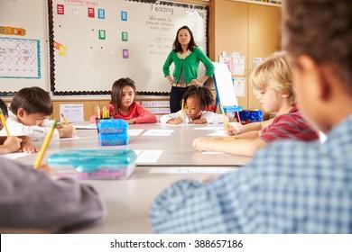 Teacher instructing elementary school kids in classroom