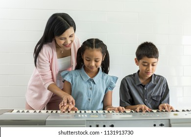 Teacher instructive or discussing with kids or pupils with friend while Learning to play Piano In Music Lesson on classroom. Music education and extra-curricular lessons concept