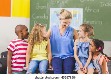 Teacher and kids having fun in classroom at school