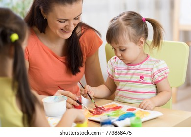 Teacher and kids little girls are painting in daycare center. Woman and children have a fun pastime.