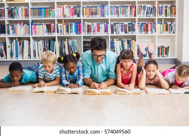 Teacher and kids lying on floor reading book in library