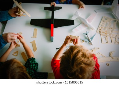 teacher and kids making toy wooden planes