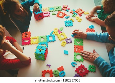 teacher and kids playing with number puzzle
