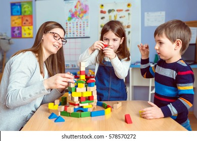 Teacher and Kids Playing Together with Colorful Toy Building Blocks