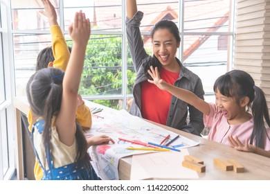 Teacher and Kindergarten students hand up for happiness