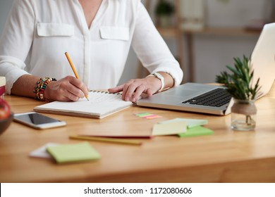 Teacher with laptop on her table taking notes in planner