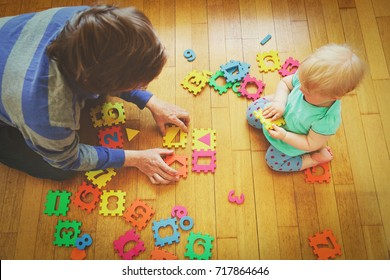 teacher and little baby playing with number puzzle