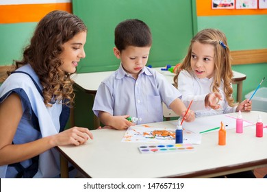 Teacher with little children painting at desk in classroom