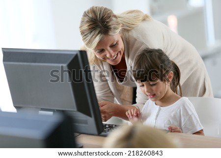 Teacher with little girl in class using computer and tablet