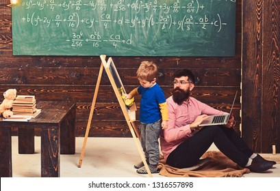 Teacher looking at kid wiping chalkboard. Side view boy and bearded man sitting on floor with laptop. Informal education concept.