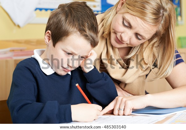 Teacher With Male Elementary School Pupil With Problem