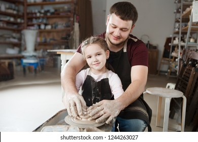 Teacher man and child girl pupil in pottery