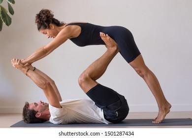 Teacher and man doing yoga exercises