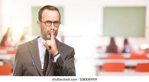 Teacher man using glasses with index finger on lips, ask to be quiet. Silence and secret concept at classroom