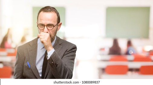 Teacher man using glasses sick and coughing, suffering asthma or bronchitis, medicine concept at classroom