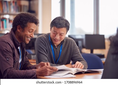 Teacher With Mature Male Adult Student Sitting At Table Working In College Library