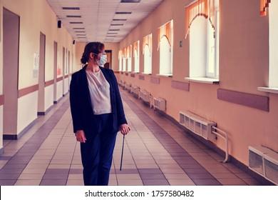 Ein Lehrer in einer medizinischen Maske steht in einem leeren Schulkorridor. Probleme bei der Ausbildung in der Quarantäne aufgrund der Epidemie des Coronavirus