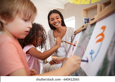 Teacher At Montessori School Helping Children in Art Class
