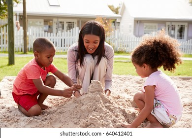 Teacher At Montessori School Playing With Children In Sand Pit
