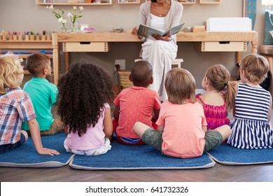 Teacher At Montessori School Reading To Children At Story Time