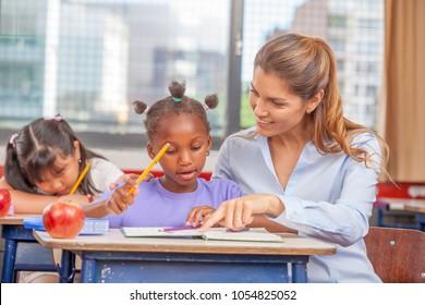 Teacher in a multi ethnic primary classroom.