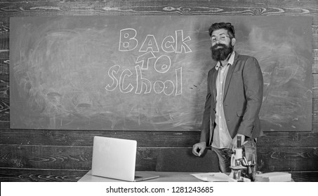Teacher passionate job ability reach out students. Teacher near chalkboard holds chalk write inscription back to school. Man bearded teacher missed his work during vacation. Back to school concept.