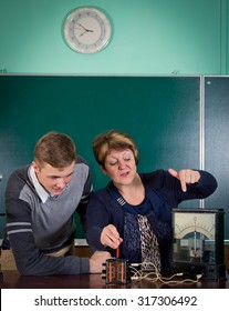 The teacher of physics explains to the pupil interaction of a magnetic field and electric field. Electrical engineering  bases
