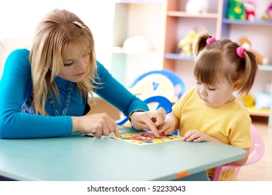 Teacher play with cute child in a playroom