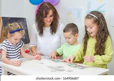 Teacher plays with children in kindergarten.