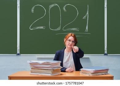 Ein Lehrer weist mit dem Text 2021 einen Finger nach vorn auf eine Tafel. Probleme mit der Schulbildung und dem Internetunterricht in der Coronavirus-Quarantäne