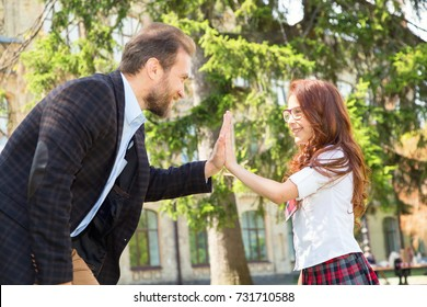 Teacher praises the student and makes cotton with his hands. Happy day the father wishes his daughter.