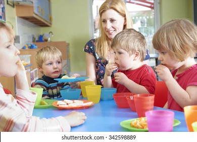 Teacher With Pre School Children Eating Healthy Snacks At Breakt